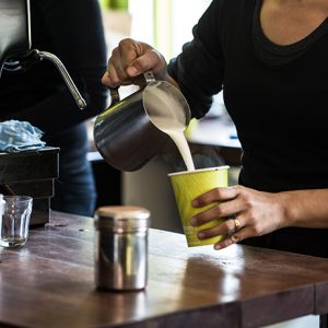 Pouring milk into takeaway coffee cup